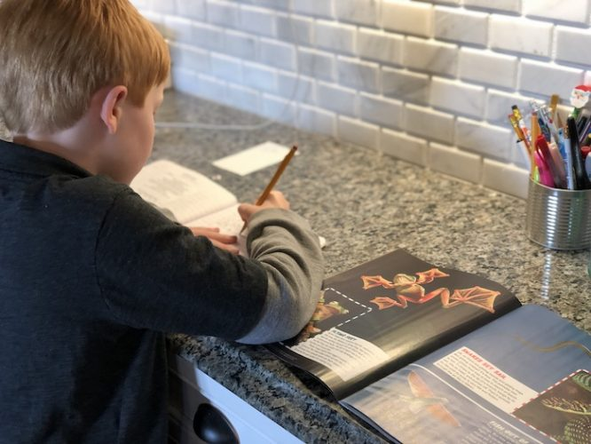 kid reading magazine and writing homework sentences