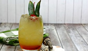 Orange and Pineapple Hawaiian Hammer layered cocktail on a green check napkin and seashell decorations