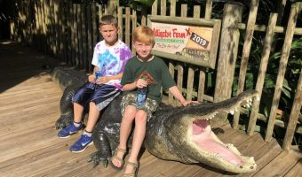 Cousins sitting on a gator replica