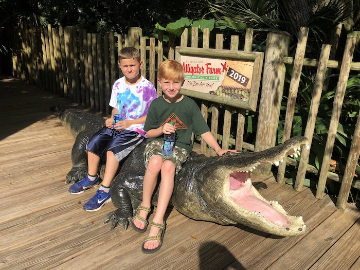 Cousins sitting on a gator replica at st augustine alligator farm