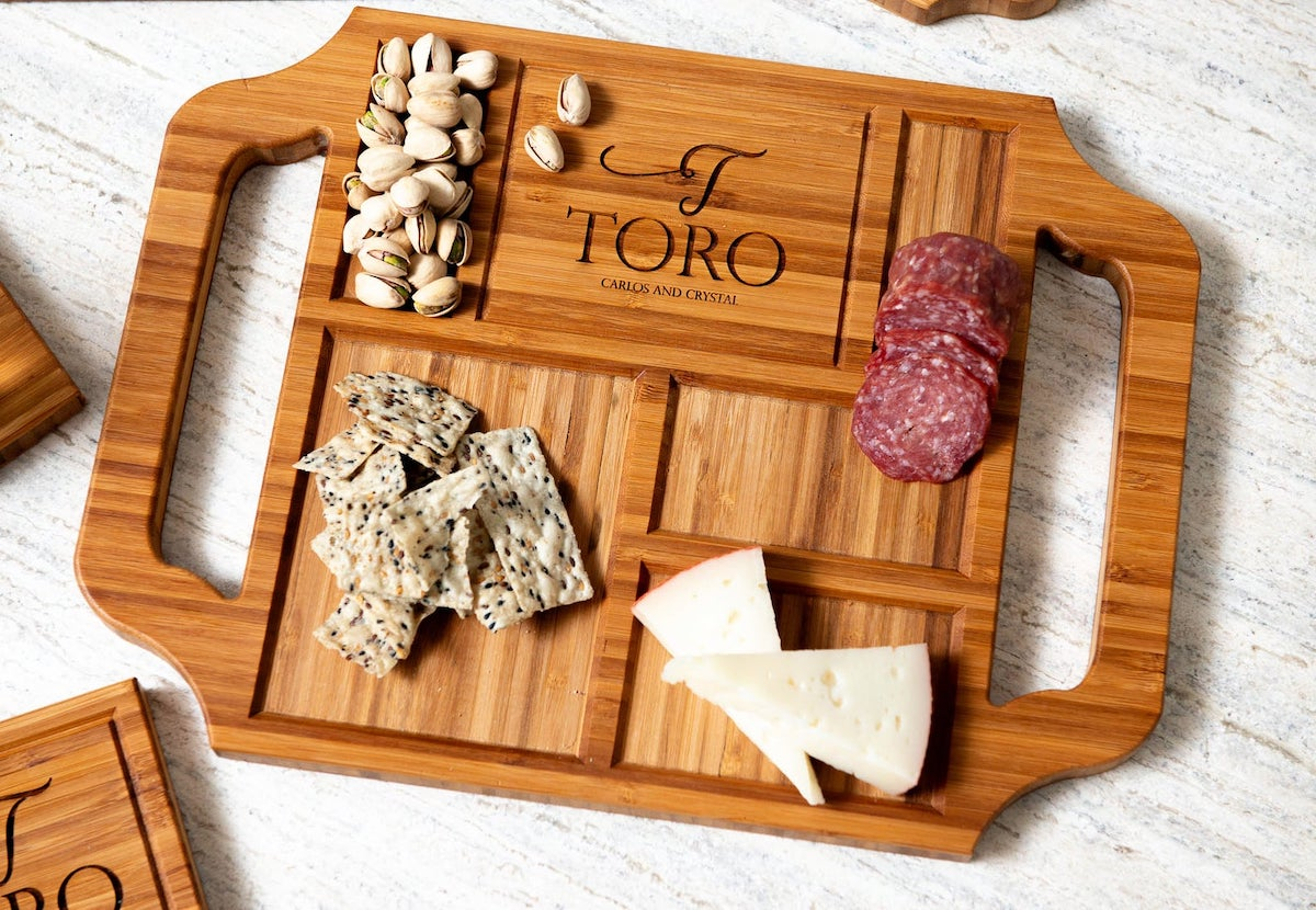 Initial and personalized burned in name on a charcuterie board decorated with fruit and cheese