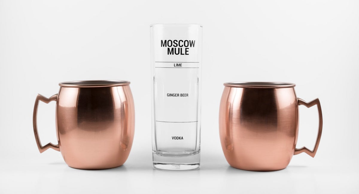 two copper moscow mule cups and a measuring glass