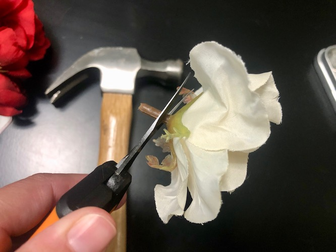 cutting fake flowers at the base